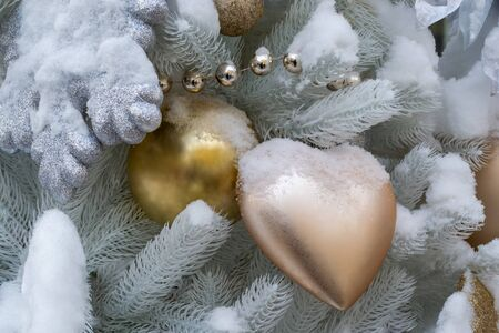 Christmas decorations. A spruce branch of unusual white color, decorated with toys in the form of a heart and a ball, gold color. Covered in snow. Close-up