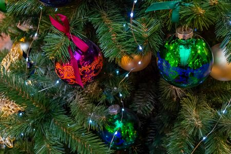 Christmas toys, balls of gold, purple and green colors, a shining garland hanging on the branch of the Xmas tree. Close-up. Banque d'images