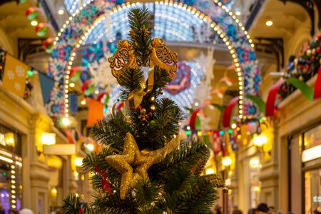 The Christmas tree is decorated with lights, toys, stars, angels, ribbons, cones. Bright, beautiful, festive interior in the background. Bokeh