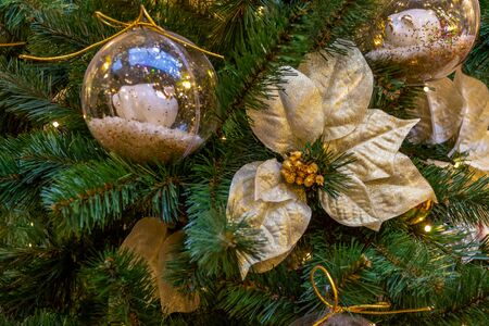 Christmas decorations. A gold flower hangs on a branch. Macro. Close-up. Xmas