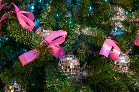 Christmas toys in the form of disco balls. and pink bows hanging on the branch of the Xmas tree. Close-up.