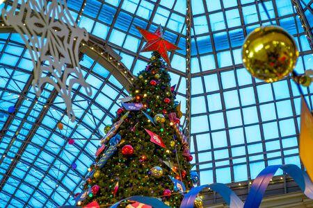 Christmas tree is decorated with lights, balls, toys and garlands, and big star of red color at the top. Indoor.