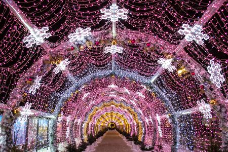 Futuristic tunnel of LED lights. Christmas lights, garland. Banque d'images