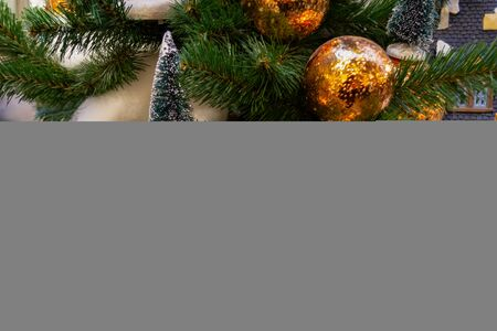Christmas toys, balls of gold and silver colors, a shining garland hanging on the branch of the Xmas tree. Close-up. Banque d'images