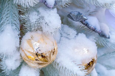 Christmas decorations. A branch of white spruce, covered with snow, toys in the form of balls hang on it. Close-up Фото со стока