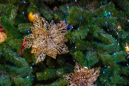 Christmas tree decoration. Golden flower, gold and blue balls, glowing garland. Close Up