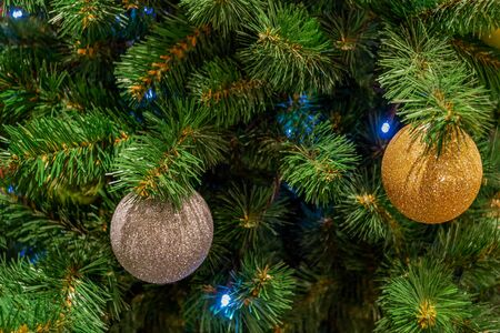 Christmas toys, balls of gold and silver colors, a shining garland hanging on the branch of the Xmas tree. Close-up. Фото со стока