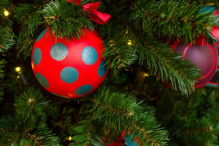 Christmas toys, balls of red, green and purple colors, shining garland on the Xmas tree. Close-up Banque d'images