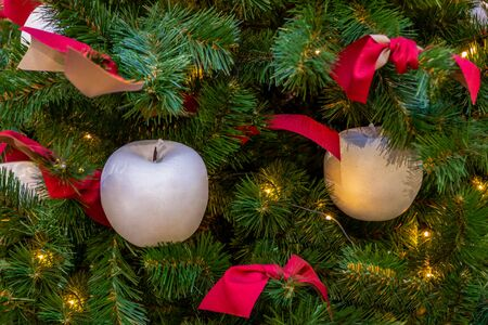 Xmas decorations. Two decorative white apples, pink bows and a shining garland weigh on the Christmas tree. Close-up.