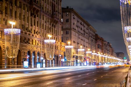 Street beautifully decorated with Christmas lights. The road goes beyond the horizon. Cars rushing at high speed. Center of Moscow on a winter evening. Banque d'images