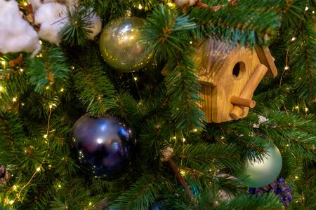 Christmas toys, balls of different colors, a birdhouse, a shining garland hanging on the branch of the Xmas tree. Close-up