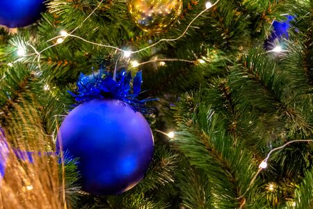 Christmas toys, balls of blue and gold colors, shining garland on the Xmas tree. Close-up