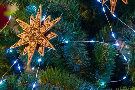 Christmas decorations. Beautiful Xmas star, and sparkling garlands decorate the branches of the Christmas tree. Close-up