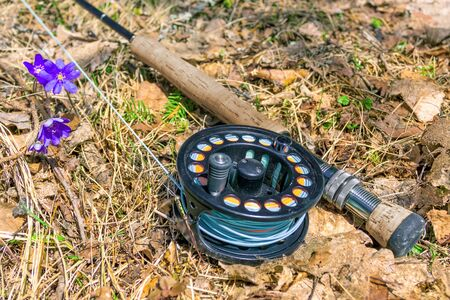 A fly fishing rod lies on dry grass Banco de Imagens