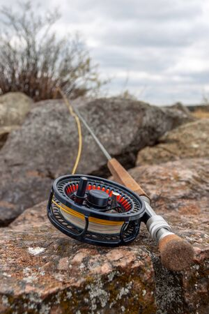A fly fishing rod lies on large stones