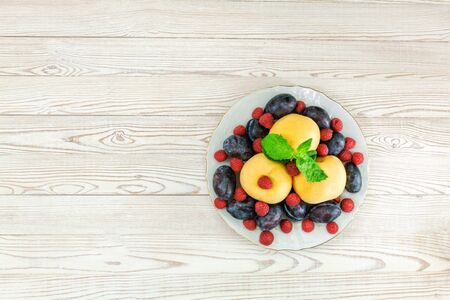 fruits and berries on a plate on a wooden light background
