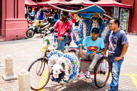 A riksha and a group of men. Rikshas in Melaka are very colorfull and use a lot of decoration and toys to attract tourist.