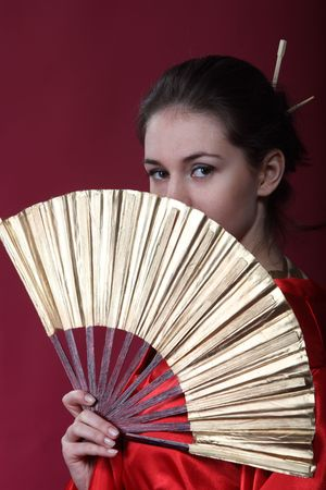 Beautiful brunette girl in a japanese kimono with the fun photo