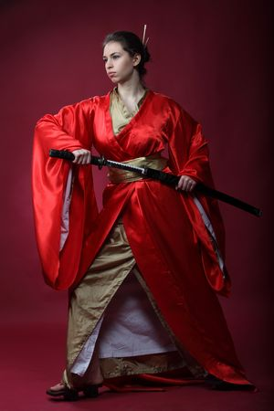 Beautiful brunette girl in a japanese kimono with katana