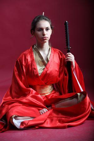 Beautiful brunette girl in a japanese kimono with katana photo