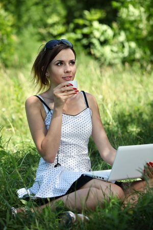Girl with a notebook drink a coffee on the glade Stock Photo - 7221059