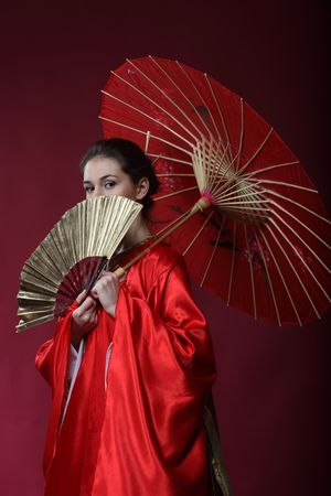 Beautiful brunette girl in a japanese kimono with an umbrella and a fun photo