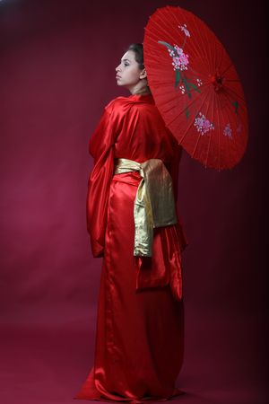 Beautiful brunette girl in a japanese kimono with an umbrella