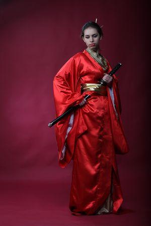 Beautiful brunette girl in a japanese kimono with a katana