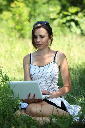 Girl with a notebook sit on the glade Stock Photo - 7231495