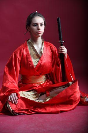 Beautiful brunette girl in a japanese kimono with a katana photo