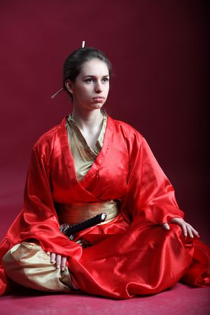 Beautiful brunette girl in a japanese kimono with a katana photo