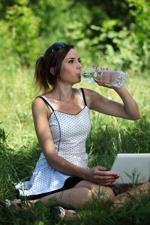 Dziewczyna z napój notebooka w wodzie mineralnej na Polana