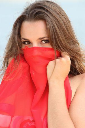 Femme avec showl rouge sur la plage de loocking dans la cam�ra