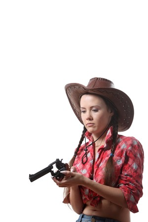 Pretty young girl in the cowboy hat with two pigtails check  his revolver photo