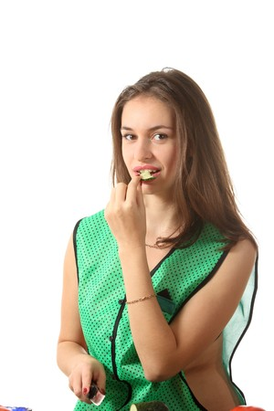 Young girl dressed in green apron eat a peace of cucumber photo