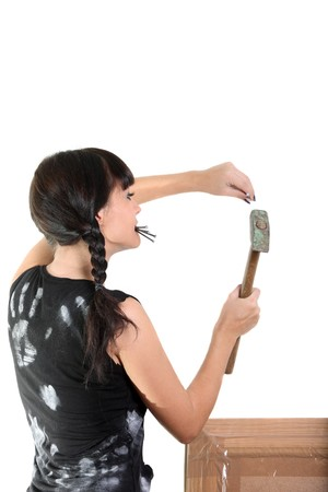 Girl hold nails in a teeth and drive in nail to the wall by hammer photo