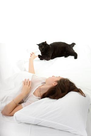 Femme dans une pi�ce de lit avec son chat noir Banque d'images