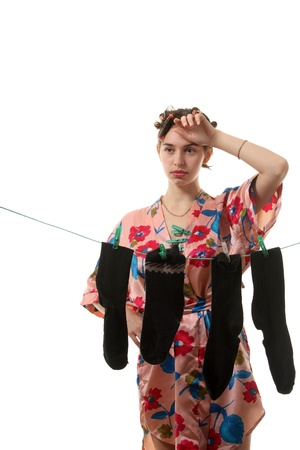 stereotypical: Young tired housewife hangs up socks on  the clothesline Stock Photo