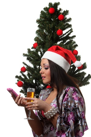Woman in a christmas hat speak mobile in front of a christmas tree photo