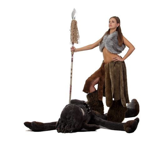 cave dweller: Young attractive savage girl with a spear kill a monster Stock Photo