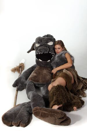 cave dweller: Young attractive girl in costume of savage woman lie with a monster