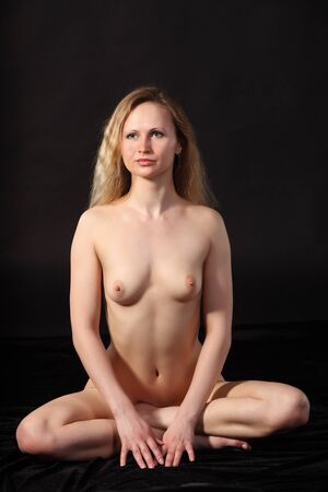 Young attractive naked woman sit in the lotos position Stock Photo - 9884290