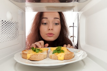 Attractive girl looks in a microwave Banque d'images