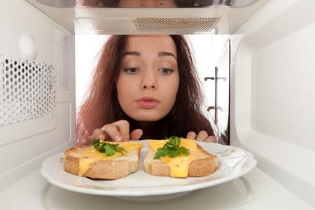 Jeune femme se regarde dans un micro-ondes Banque d'images