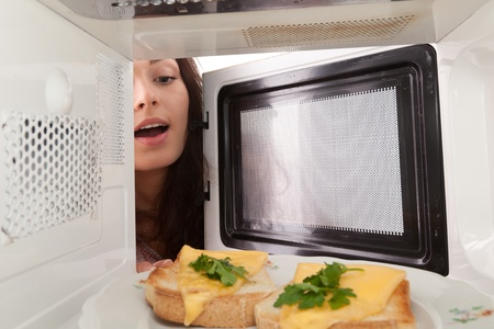 Attractive girl open  a microwave photo