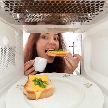 Atrakcyjna dziewczyna jeść kanapkę z kuchenką mikrofalową