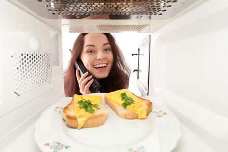 Attractive girl looks in a microwave and speak phone