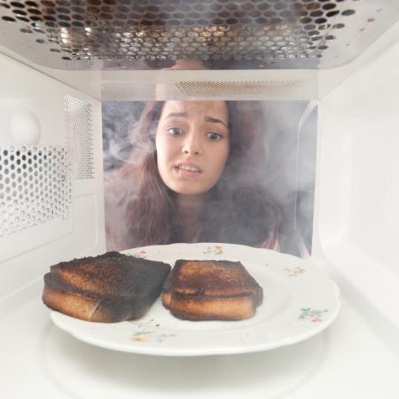 Młode grzanki palić dziewczyna w kuchence mikrofalowej