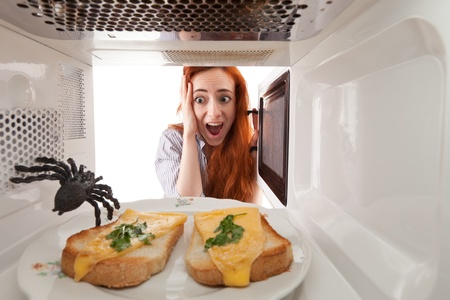 Girl saw spider in a microwave Stock Photo