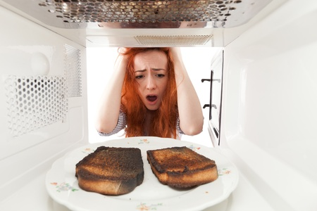 smut: Girl look to a burned toasts in microwave Stock Photo